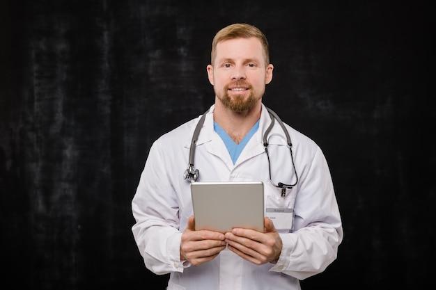 Gelukkige jonge bebaarde arts in whitecoat die digitale tablet door borst houdt terwijl hij u tegen zwarte achtergrond bekijkt