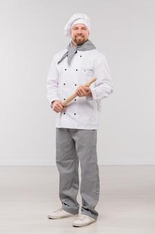 Gelukkige jonge bebaarde chef-kok die in uniform houten deegroller houdt terwijl hij geïsoleerd voor camera staat