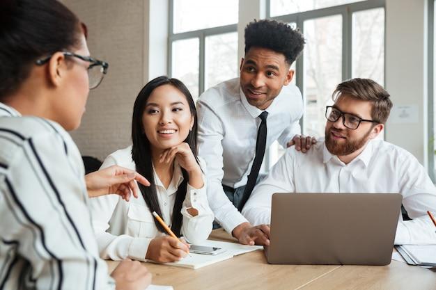 Gelukkige jonge bedrijfscollega's die laptop computer met behulp van die met elkaar spreken.