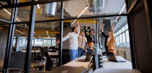 Gelukkige jonge bedrijfsmensen die zich in het bureau bevinden en op succes in het bureau verheugen