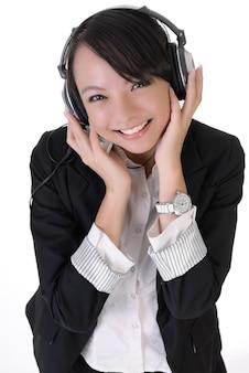 Gelukkige jonge bedrijfsvrouw die van muziek geniet en blije glimlachende uitdrukking toont.