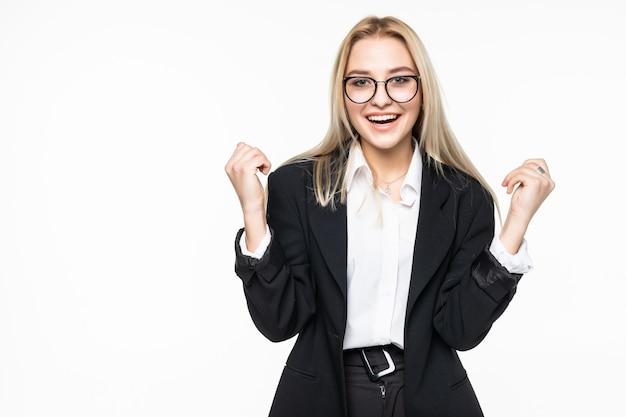 Gelukkige jonge bedrijfsvrouw die winnaargebaar doet, die ogen het gesloten stellen houdt geïsoleerd op grijze muur