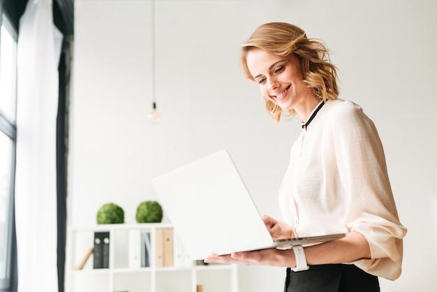 Gelukkige jonge bedrijfsvrouw die zich in bureau bevindt