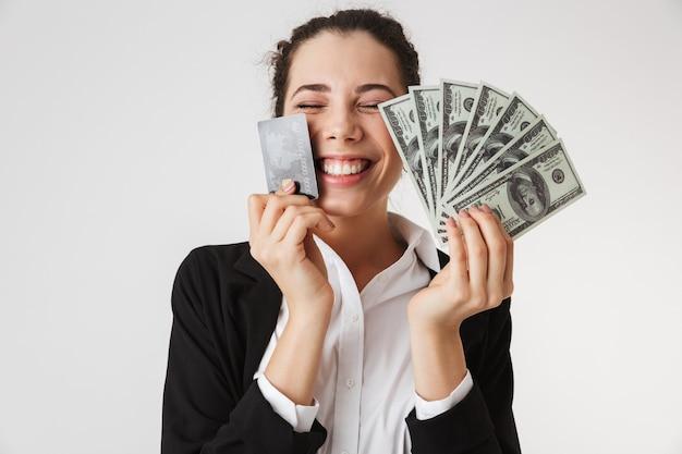 Gelukkige jonge bedrijfsvrouw met creditcard en geld