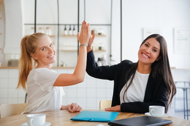 Gelukkige jonge bedrijfsvrouwen die high five geven en succes vieren, aan tafel zitten met documenten en koffiekopjes, camera kijken