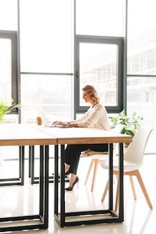 Gelukkige jonge bedrijfsvrouwenzitting in bureau dat laptop met behulp van