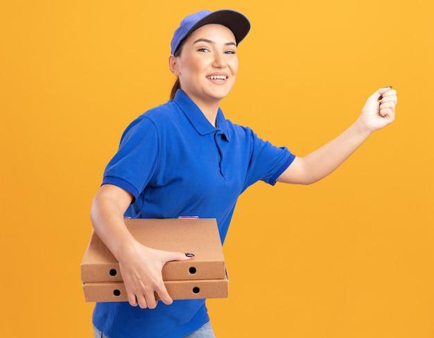 Gelukkige jonge bezorger in blauw uniform en pet haast zich rennen voor het bezorgen van pizzadozen voor klant over oranje muur