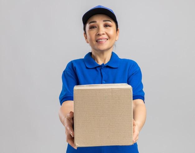 Gelukkige jonge bezorger in blauw uniform en pet met kartonnen doos met een glimlach op het gezicht die over een witte muur staat