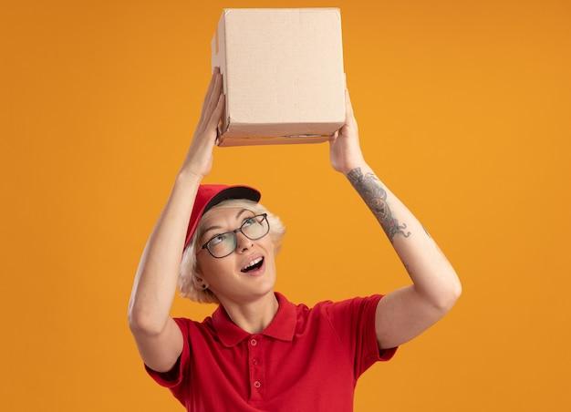 Gelukkige jonge bezorger in rood uniform en pet die een bril draagt die een kartonnen doos boven haar hoofd houdt en ernaar kijkt met een glimlach op het gezicht staande over de oranje muur