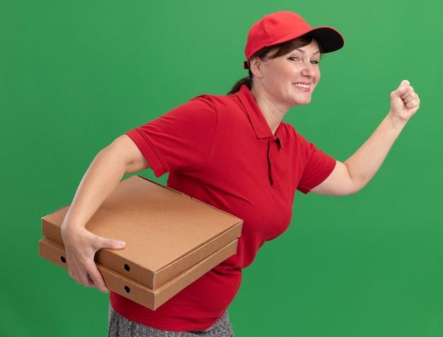 Gelukkige jonge bezorger in rood uniform en pet haast zich rennen voor het bezorgen van pizzadozen voor klant over groene muur