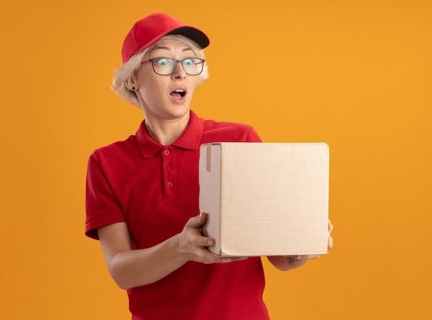 Gelukkige jonge bezorger in rood uniform en pet met bril met kartonnen doos kijken verbaasd en verbaasd staande over oranje muur