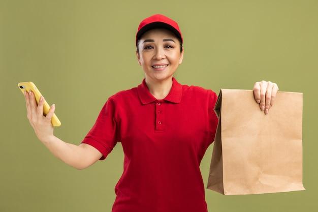 Gelukkige jonge bezorger in rood uniform en pet met papieren pakket en smartphone met een glimlach op het gezicht die over de groene muur staat