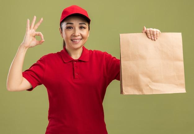 Gelukkige jonge bezorger in rood uniform en pet met papieren pakket met een glimlach op het gezicht en doet een goed teken
