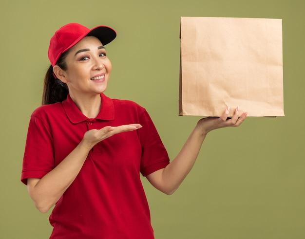 Gelukkige jonge bezorger in rood uniform en pet met papieren pakket met glimlach op gezicht presenterend met arm van hand over groene muur