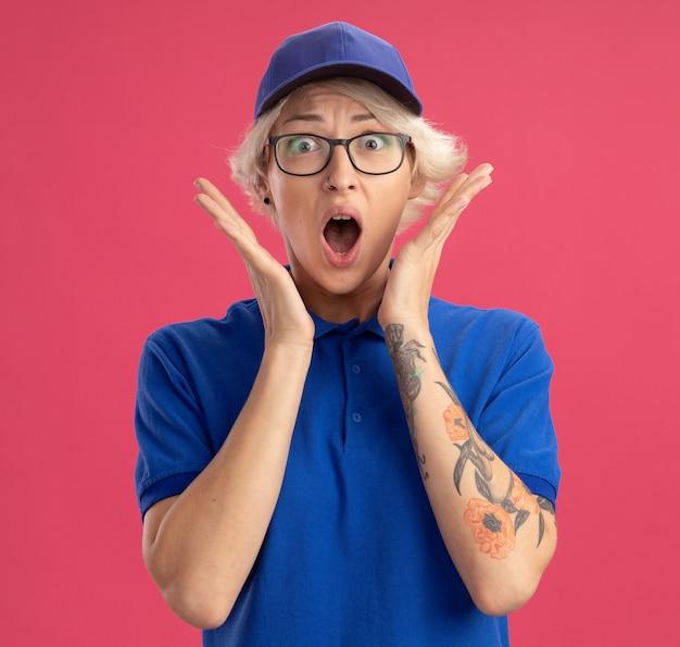 Gelukkige jonge bezorgvrouw in blauw uniform en pet die met wijd open mond wordt geschud die zich over roze muur bevindt