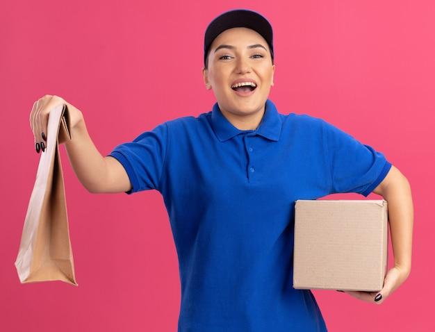 Gelukkige jonge bezorgvrouw in blauw uniform en pet met papieren pakket en kartonnen doos die naar de voorkant glimlachend vrolijk staande over roze muur kijken