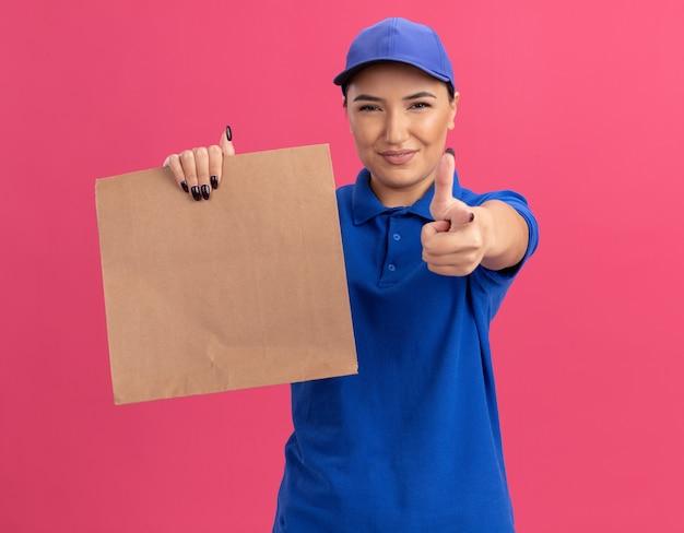 Gelukkige jonge bezorgvrouw in blauw uniform en pet met papieren pakket wijzend met wijsvinger aan de voorkant glimlachend zelfverzekerd staande over roze muur Gratis Foto