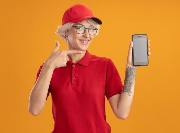 Gelukkige jonge bezorgvrouw in rood uniform en pet die een bril draagt die smartphone toont die met wijsvinger ernaar richt die vrolijk glimlacht over oranje muur staat