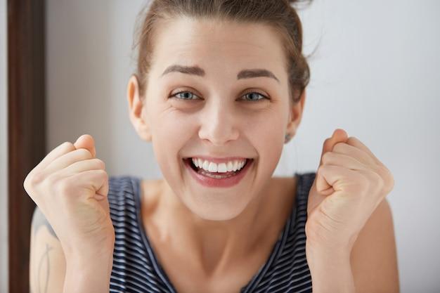 Gelukkige jonge blanke vrouw die barst van vreugde en plezier. mooi meisje met blauwe ogen verdubbelt haar vuisten in winnende mentaliteit, lacht met wijd open mond en toont haar perfecte witte tanden.