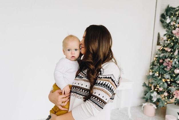 Gelukkige jonge blanke vrouw die haar baby kust