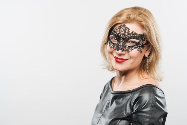 Gelukkige jonge blonde dame in masker