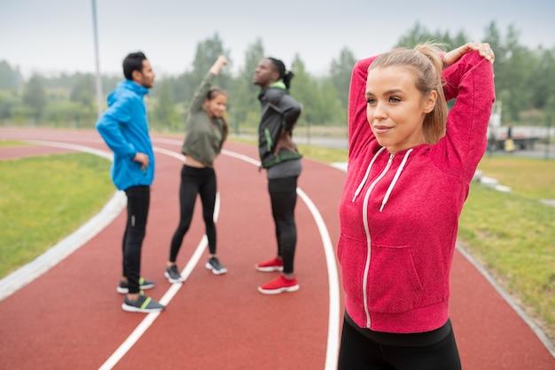 Gelukkige jonge blonde sportvrouw die opwarmingsoefening op stadion van haar vrienden vóór marathon doen