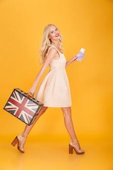 Gelukkige jonge blonde vrouw die britse gedrukte koffer houdt