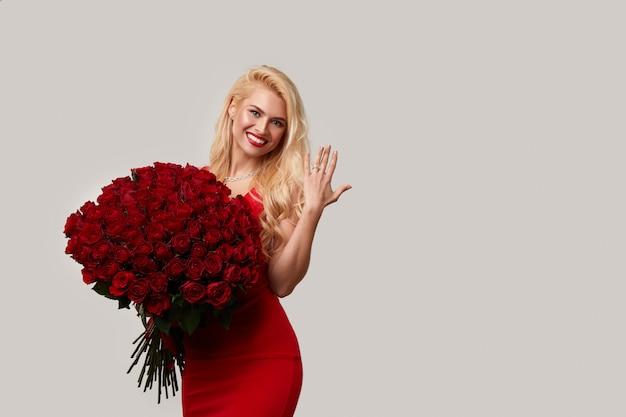 Gelukkige jonge blonde vrouw die een groot boeket van rode rozen als een geschenk voor 8 maart of valentijn. ze wijst naar de verlovingsring om haar vinger.