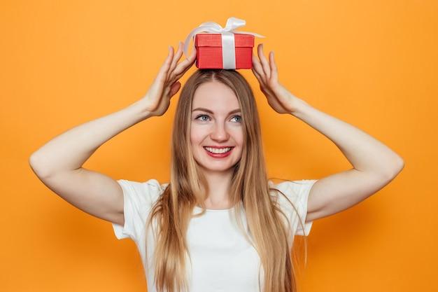 Gelukkige jonge blonde vrouw die een rode giftdoos boven haar hoofd houdt die op gele muur wordt geïsoleerd