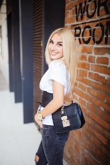 Gelukkige jonge blonde vrouw die met rug glimlacht en in vrijetijdskleding draagt die tegen bureaubakstenen muur kijkt