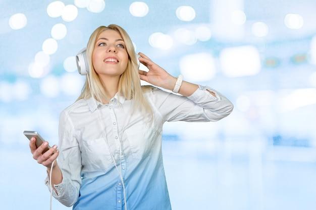 Gelukkige jonge blonde vrouw die naar muziek luistert