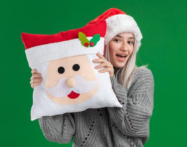 Gelukkige jonge blonde vrouw in de wintertrui en santahoed die kerstmishoofdkussen houden die camera met glimlach op gezicht bekijken die zich over groene achtergrond bevinden