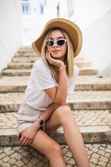 Gelukkige jonge blonde vrouw in hoed en zonnebril
