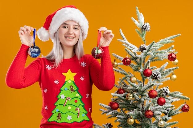 Gelukkige jonge blonde vrouw in kersttrui en kerstmuts met kerstballen die vrolijk glimlachen naast een kerstboom over oranje muur