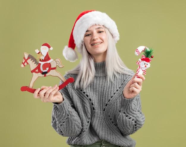 Gelukkige jonge blonde vrouw in wintertrui en kerstmuts die kerstspeelgoed vasthoudt met een glimlach op het gezicht dat over een groene muur staat