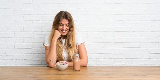 Gelukkige jonge blonde vrouw met kom van granen