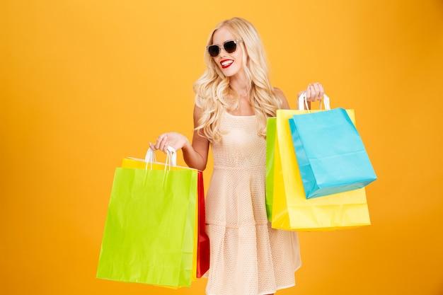 Gelukkige jonge blonde vrouwenholding het winkelen zakken.
