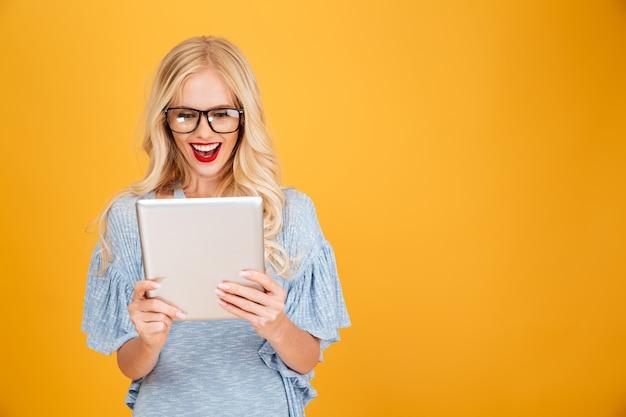 Gelukkige jonge blondevrouw die tabletcomputer met behulp van.