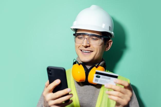 Gelukkige jonge bouwersman, ingenieur, online betalen met smartphone en creditcard. bouwveiligheidshelm, bril en koptelefoon dragen op de muur van aqua menthe kleur.