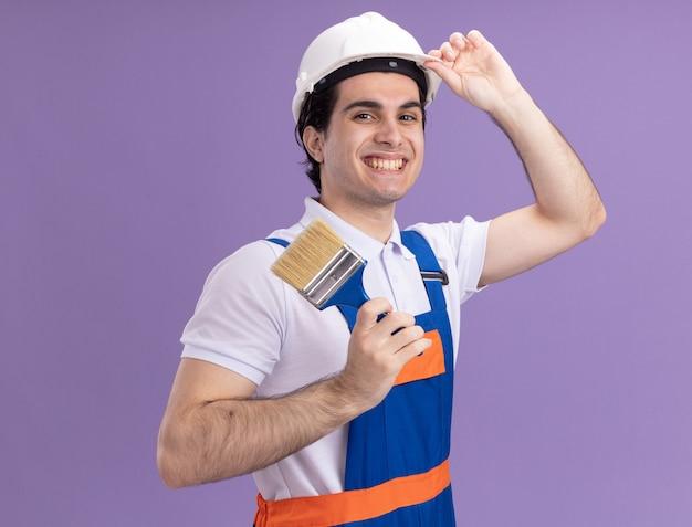 Gelukkige jonge bouwersmens in bouwuniform en veiligheidshelm die verfborstel houden die voorzijde glimlachend zelfverzekerd over purpere muur bekijken