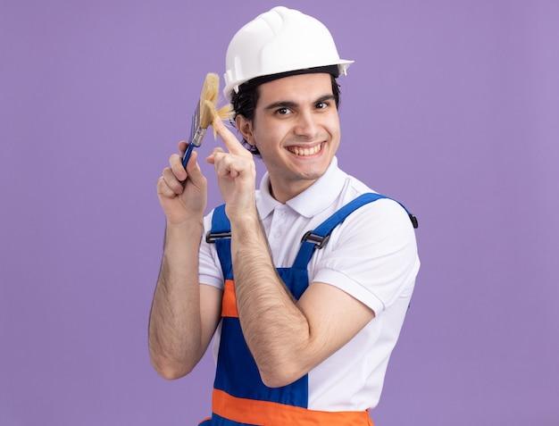Gelukkige jonge bouwersmens in bouwuniform en veiligheidshelm die verfborstel houden die voorzijde met grote glimlach op gezicht bekijken die zich over purpere muur bevinden