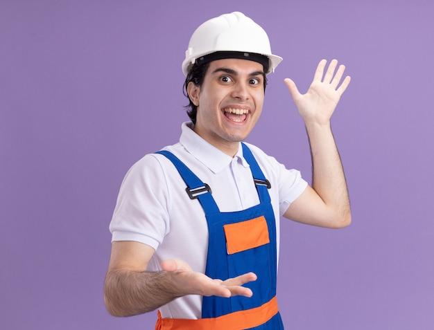 Gelukkige jonge bouwersmens in eenvormige bouw en veiligheidshelm die voorzijde gebaren met handen bekijken die vrolijk glimlachen die zich over purpere muur bevinden