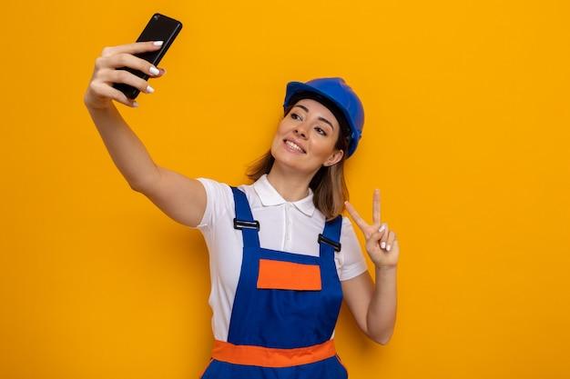 Gelukkige jonge bouwvrouw in bouwuniform en veiligheidshelm die vrolijk lacht en v-teken toont die selfie maakt met smartphone