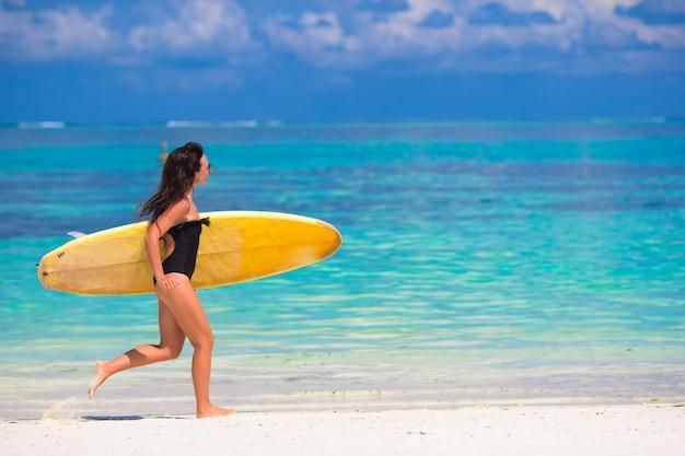 Gelukkige jonge brandingsvrouw die bij het strand met een surfplank loopt