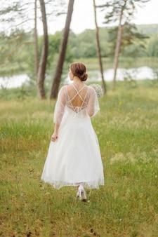 Gelukkige jonge bruid in een dennenbos witte trouwjurk