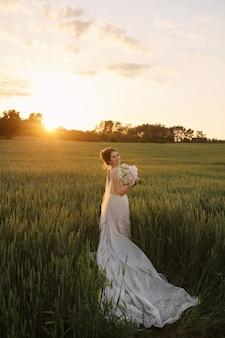 Gelukkige jonge bruid in witte kanten jurk poseren met bruids boeket bloemen in de wei op de zonsondergang
