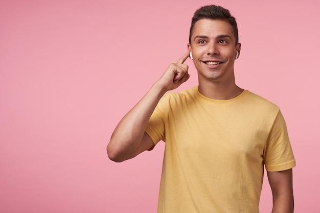Gelukkige jonge bruinogige donkerbruine man die vrolijk lacht terwijl hij naar muziek luistert en de vinger op zijn oortje houdt, staande tegen een roze achtergrond