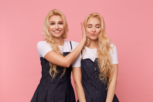 Gelukkige jonge bruinogige langharige vrouw die breed lacht terwijl ze naar de camera kijkt en de oren van haar mooie blonde zus bedekt terwijl ze haar verrast, geïsoleerd op roze achtergrond