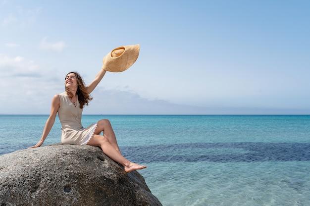 Gelukkige jonge casual vrouw genieten van de zon en frisse lucht zittend op een rots in de zee met doorschijnend helder water.