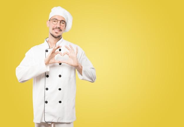 Gelukkige jonge chef-kok die een gebaar van liefde met zijn handen doet
